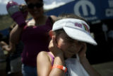 Ciarra Medina, 6, of Englewood plugs her ears as a top fuel car revs its engine in pit row on...