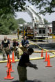 Firefighters proceed to a decontamination area after a fire at Circuits West in Longmont, Colo.,...