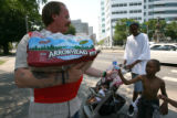 Ray Christenson, cq, (left) of The Salvation Army, hands a bottle of  water to Kalabb Maso, cq, 6,...