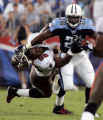 Tennessee Titans running back Travis Henry (20) stiff arms the helmet off of Tampa Bay Buccaneers...