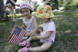 Chloe Richmond, 4,(left)  and her sister Elise, 2, switch flags while listening to music during...