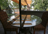 A glass top table reflects the top, called a pergola design, of the new wood deck, which extends...
