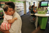 April Bonilla (CQ), 6 months, is held by her uncle Eric Infante as he waits in line at the...