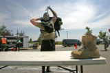 142 SGT. Shawn Miller, of the 8th Civil Support Team, Colorado National Guard, undresses from his...