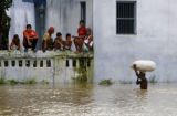 PAT101 - Villagers watch another shifting grain to safer areas through floodwaters in Fatehpur...