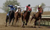 Horses turn the corner into the homestretch at Arapahoe Park Racetrack in Aurora. Monday July 10,...