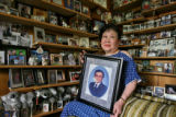 DLM0004  Surrounded by photographs representing a lifetime of memories and holding a photograph of...