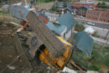 A Backhoe used to build up the rock wall above Church Street in Black Hawk., Colo., rests on it's...