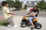 Vince Sanchez, 10, riding with his mom on his battery deceased vehicle gets a pullstart by his...