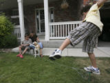 Vince Sanchez, 10 and mom Lori play with the family dog, Stanford, as brother Evan, 8, tries to...