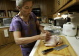 Joy Romero Meyers (cq) skins a chicken with a razor blade while making a Filipino stuffed chicken...