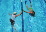 Molly Bloom (cq), 19, left, slaps hands with her sister Katie Casper (cq), right, as they swim at...