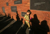 Austin Overholt (cq), 7, walks past the plaques with a flower at the dedication ceremony for the...