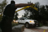 Denver Police officer Damon Marquez (cq) lifts the police  tape as a caravan of vehicles drive...