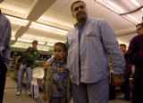 Al Taei Nazar Salah Aldeen Sharif and his son wait for their families luggage sometime after 12:30...