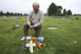 David Crowfoot, Edgewater, Colo. native,  kneels above the gravesite where Chandler A. Grafner, 7,...