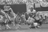 Broncos quarterback John Elway is hit by the Baltimore Colts after releasing the ball