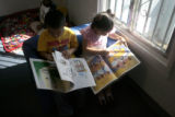 Ramiro Gutierrez-Ruiz, 4, left, and Leianl-Nalee Maderas, 4, read books at the Northeast Mile High...