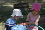 Marina Garlick, 3 and her brother, Seth, 2 work together to fill a container at their home in ...