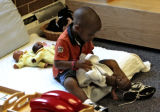 Gerald Love, 3, cleans a doll at the Mile High Montessori Edna Oliver Child Care Center, 2851...