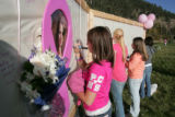 Friends of Emily Keyes write on a wall of remembrance as  the community of came together for...