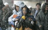 Blaire Maryboy (cq) (center w/ blanket) and classmate Shawnarae Lee (cq) (on left in blue coat)...