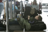 Lucas Neujahr,7 from Kalamazoo, Michigan sleeps in line at the United ticket office at Denver...