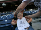 [ES1815]Josh Ayers of Philadelphia, PA.,  puts a bib on his son Ethan Ayers (CQ), 4 months, held...