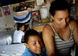 A Honduran woman sews a blanket as her son looks on. Women who can afford sewing machines often...