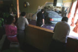 Workers of the Mesob Ethopian Restaurant  and a Denver Police Officer watch as a  car is removed...