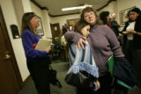 Alyssa Cao(cq)(center), 15, a freshman at Thomas Jefferson High School gets a hug from her mother...
