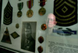 DLM1426  WWII veteran Don Haynie, 82, can be seen reflected in the glass of a frame containing an...