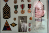 DLM1427  WWII veteran Don Haynie, 82, can be seen reflected in the glass of a frame containing an...