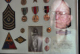 DLM1428  WWII veteran Don Haynie, 82, can be seen reflected in the glass of a frame containing an...