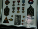 DLM1425  WWII veteran Don Haynie, 82, can be seen reflected in the glass of a frame containing an...