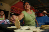 A woman makes tortillas in the market at Puerto Barrios in Guatemala on Aug. 25.  Puerto Barrios,...