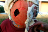A boy wears a mask made from an old soccer ball and some cloth in Yoro, Honduras.