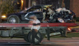 A tow truck driver (UNK) loads a Honda that was hit by a hit-and- run driver in a truck at the...