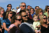A girl holds a flower as people waqtch the dedication ceremony for the Columbine Memorial at...