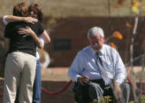 Two persons hug next to Robert Easton, Chairman of the Columbine Memorial Committee, right, as...