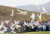 Family members watch as 200 doves are released at the dedication ceremony for the Columbine...
