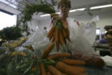 Debora Palizzi, (cq) bags carrots for a customer at Palizzi Farm in Brighton, Colo. on Monday...