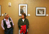 Cathi Woodward (cq), left, looks at a photo of a married couple while standing next to June Hansen...