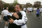 Sarah Ramos (cq), center, of Littleton, hugs Tara Abeita (cq), left, of littleton, at the finish...