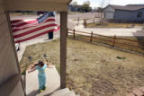 (COLORADO SPRINGS, Colo., April 14, 2005) Charlotte Keller (cq), 3, plays beneath a U.S. flag...