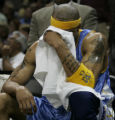Denver Nuggets Kenyon Martin holds his head in a towel on the bench in the closing minutes of the...