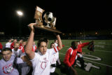Class 5A Boys Soccer State Championship Game, Denver East, Sharod Dadgar carries the trophy after...