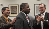 Representative Terrance Carrol, center, is congratulated by Representative Joe Rice, left, and...