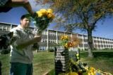 BG0300 Christian Lopez lays a boquett of flowers at a memorial in front of the school for  fellow...