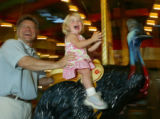 (Denver, Colo., May 20, 2005) Brad Ham and his daughter, Tate (2), take a ride on the carousel. ...